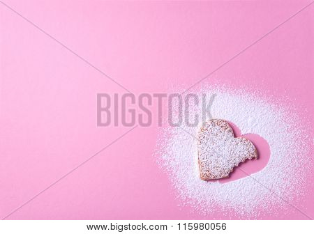 Heart Shaped Cookie With Sugar Icing On A Pink Paper Background Taken A Bite From It