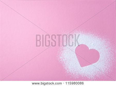 Heart Shape Made Of Icing Sugar On Pink Grainy Paper Surface