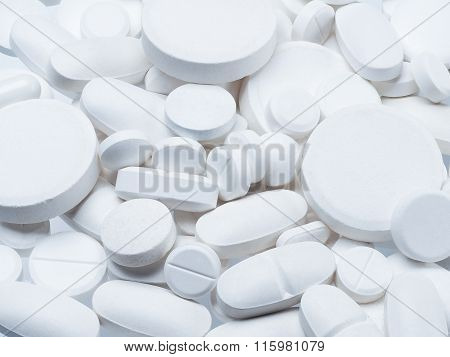 Many white pills of different size. Background of white pills, medicines