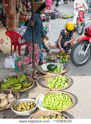 Woman picks oranges at the wet market