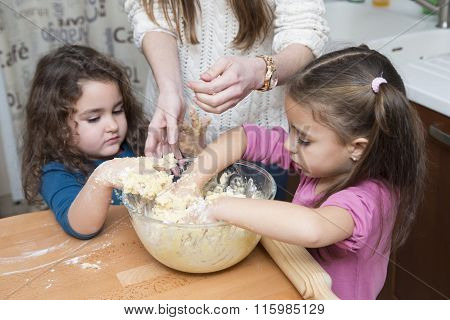 Two Lovely Girls And Mother Mixing Dough With Hands