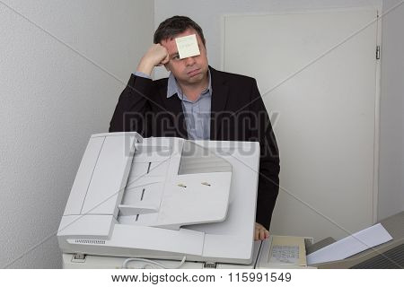 Man Near Copier With A Paper Out Of Order On His Face