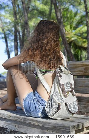 Brunette Sitting On A Park Bench In Summer