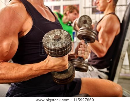 Group of handsome men in black working with heavy dumbbells his body at gym.