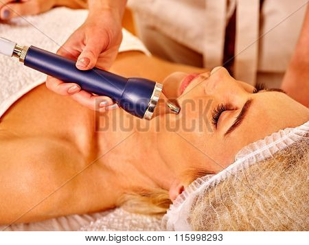 Young woman receiving electric ultrusound facial massage with blue device  at beauty salon.