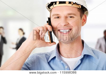 Contractor in hardhat talks on his cell phone.