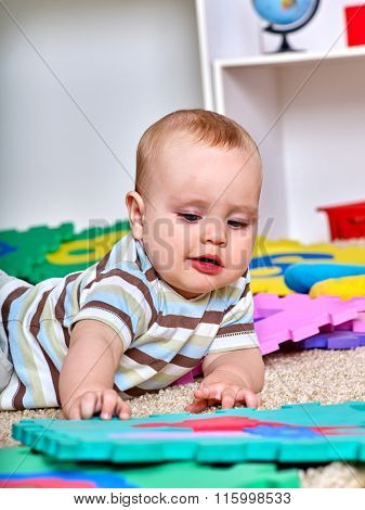 Portrait of kid baby boy lying on floor and plying with puzzle toy.