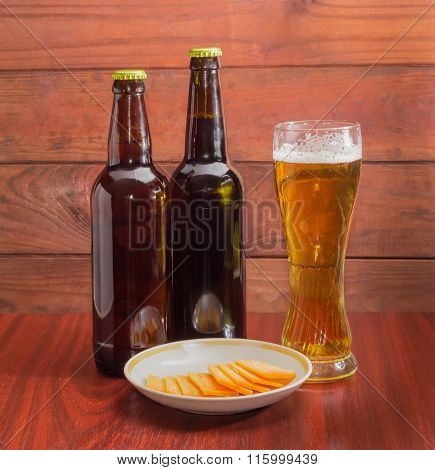Glass And Two Bottles Of Beer, Cheese On Wooden Surface