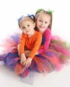 pic of tutu  - Two adorable sisters dressed in bright colorful tutus sitting down hugging each other isolated on white