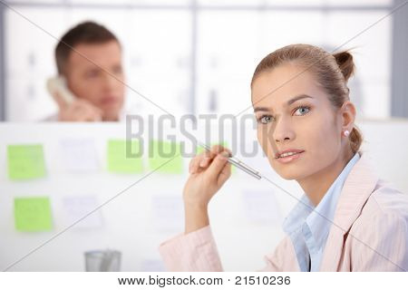 Pretty young female office worker sitting at desk in office, man in background.?