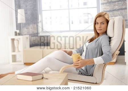 Portrait of pretty woman having tea, sitting in armchair in bright living room, smiling at camera.?