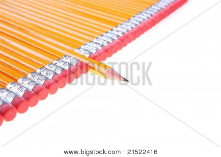 A picture of a sharp yellow pencil standing out from the row of other pencils over white background