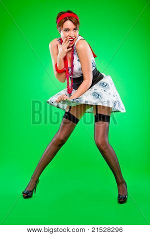 Flirty looking sensual girl holding dress blown up by wind. Pin up and retro style.