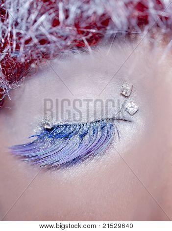 concepto de maquillaje de invierno Navidad en ojo cerrado de la mujer de pelo plateado azul y rojo