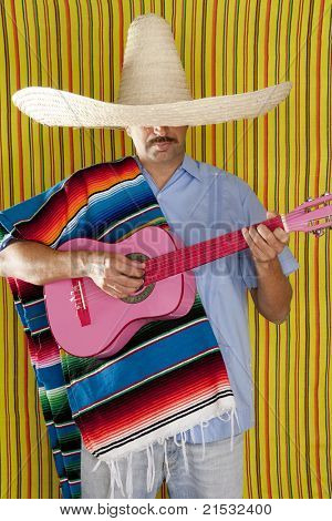 Mexican man with poncho and sombrero playing guitar typical of Mexico
