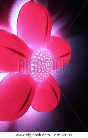 Funky and bright abstract pink flower light against black background