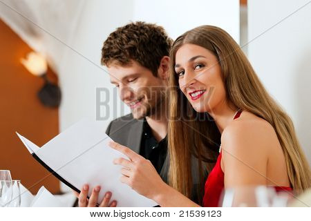 Couple looking into menu of restaurant for their dishes