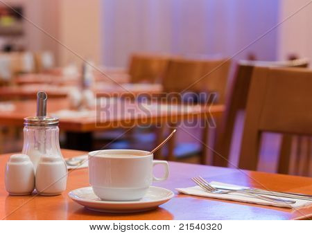 Close up of a cup of coffee on a table set for breakfast in a hotel cafe/restaurant/dining hall