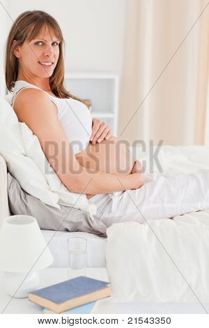 Portrait Of A Beautiful Pregnant Female Posing While Lying On A Bed