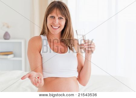 Portrait Of An Attractive Pregnant Female Taking A Pill While Sitting On A Bed