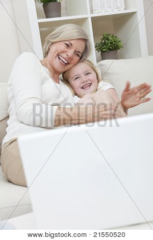A senior woman grandmother and her young child granddaughter laughing and having fun at home with a laptop computer