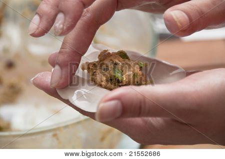 Asian woman preparing some meat dumplings