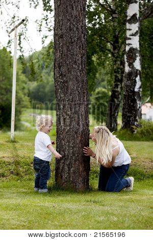 Mother and son playing hide and seek outdoors in a rural setting