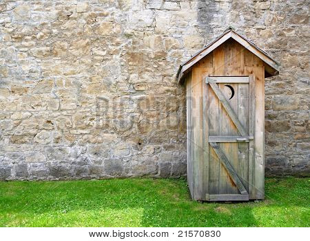 Rustic outhouse and vintage stone wall
