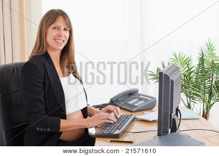 Lovely pregnant woman working with a computer at the office