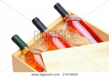 Closeup of three blush wine bottles on their side in a wooden crate. Crate lid is pulled partially back exposing the bottles and packing excelsior. Horizontal format isolated on white.