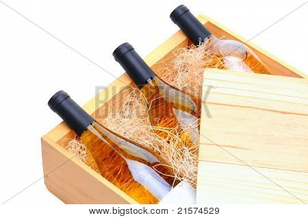 Closeup of three white wine bottles on their side in a wooden crate. Crate lid is pulled partially back exposing the bottles and packing excelsior. Horizontal format isolated on white.