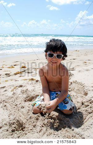 An adorable Hispanic boy plays in the sand