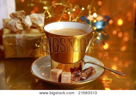 Coffee in gold cup with brown sugar