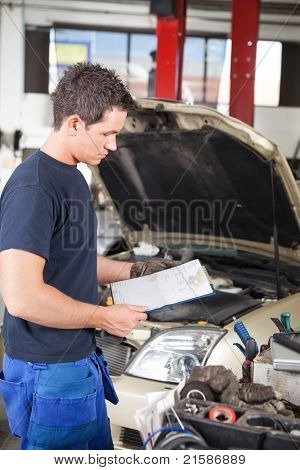 Three-quarter length of mechanic holding a work order