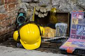 Construction Tools For Building A House On A Stone Wall. Hammer, Helmet, And Other Necessary Tools F poster