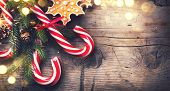 Christmas Holiday Background with Gingerbread cookies, Candy Cane and evergreens border over wooden  poster