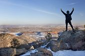 stock photo of horsetooth reservoir  - silhouette of happy male hiker standing on a rock and looking down to Horsetooth Reservoir town of Fort Collins and Colorado plains typical hazy winter scenery - JPG
