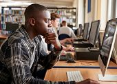 Male Student Working On Computer In College Library poster