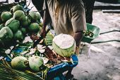 Man handing in a green coconut. Coconut cutter. Natural fruity diet. Traditional local agriculture o poster