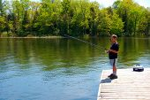foto of dock a pond  - Young boy Fishing from a dock in a river - JPG