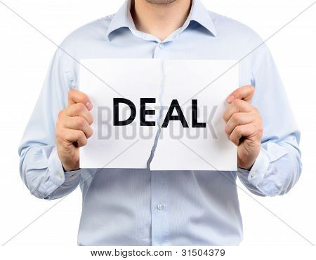 "Man Holding A Torn Paper Which Says ""deal"""