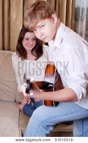 Teenage Boy Playing By Guitar