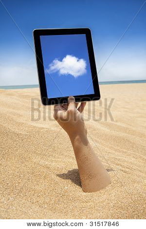 Hand Holding Touch Screen Computer On The Beach