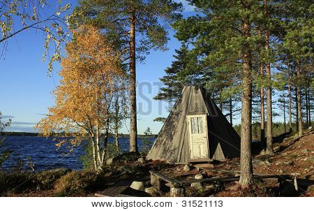 Autumn by a wooden tipi.