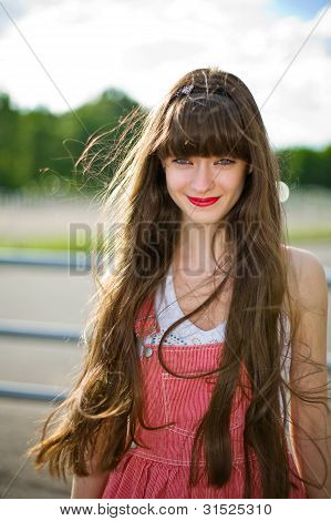 A beautiful girl with long hair coquettishly smiling
