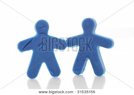Two Blue People Shaped Molding Dough Figures Against White Background