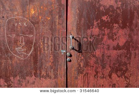 Graffit and peeling paint on old red steel door