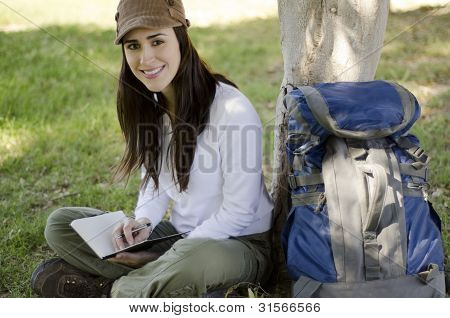 Young woman writing on travel journal