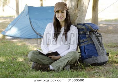 Young woman writing on a travel journal