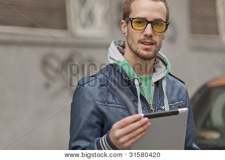Man on street with tablet computer